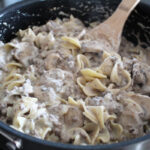a pan with Ground Beef Stroganoff in it with a wooden spoon scooping into it