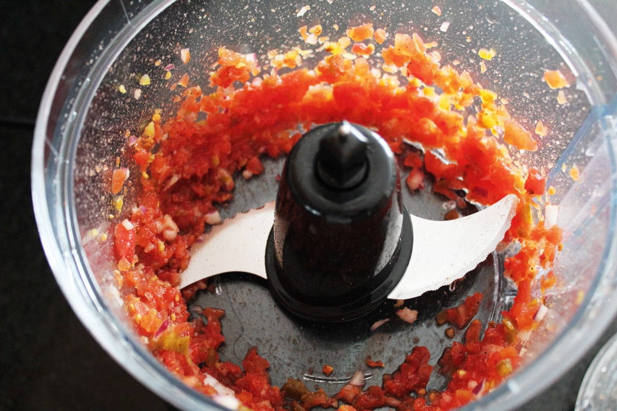 fresh salsa ingredients in a food processor shot from overhead