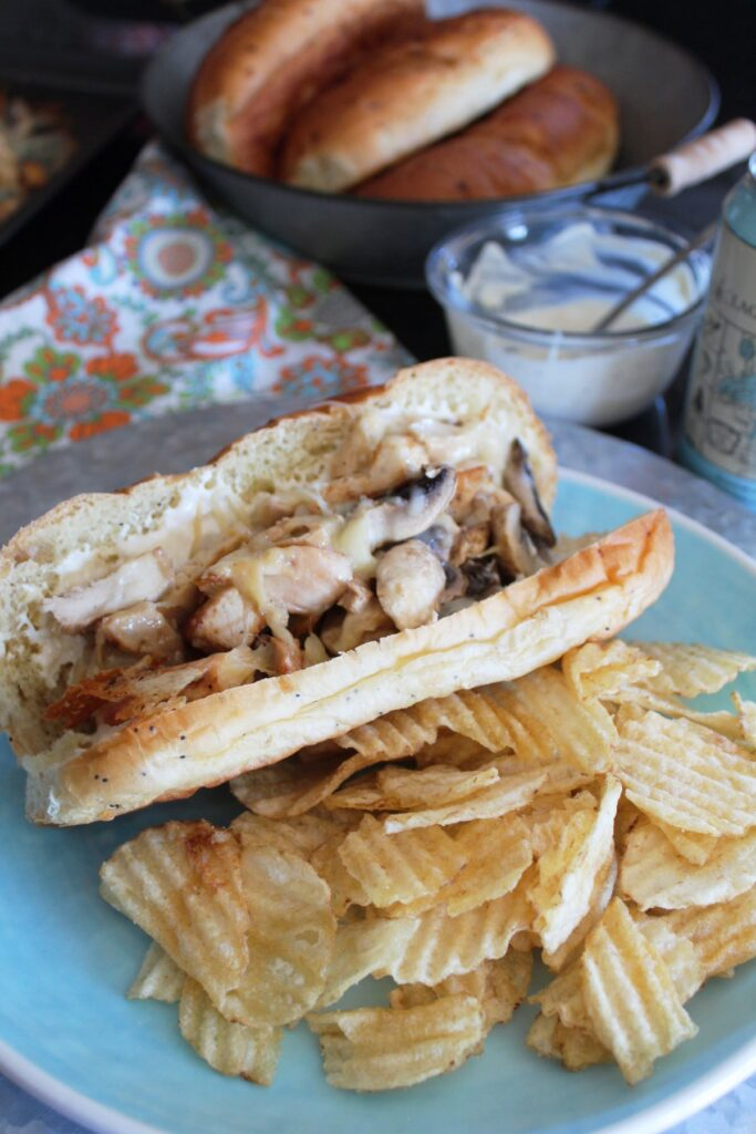 long side shot of a plate with a chicken and mushroom sub and potato chips on it. in the background is a craft beer a plate of sub buns and a dish of sauce.