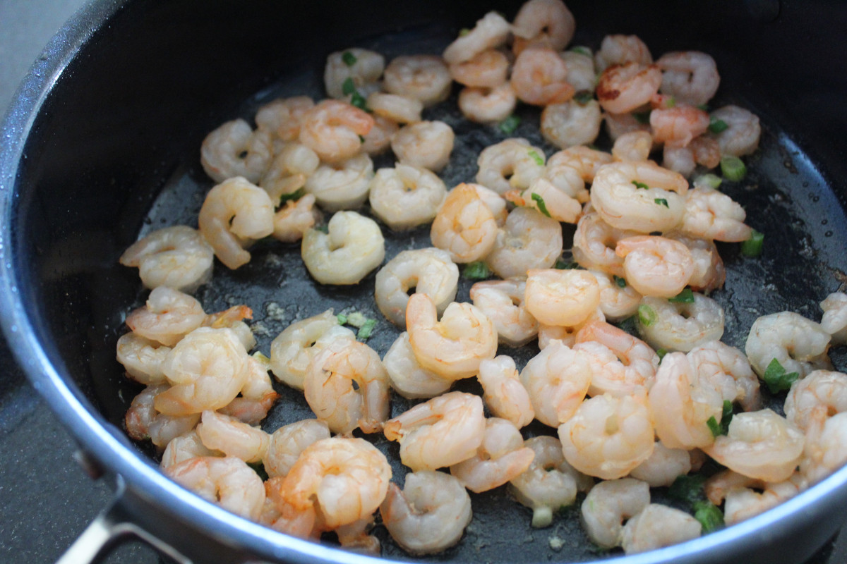 Shrimp and green onions cooking in a pan.