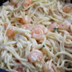 a side shot of a pan of prepared shrimp spaghetti with a creamy mayo based sauce.