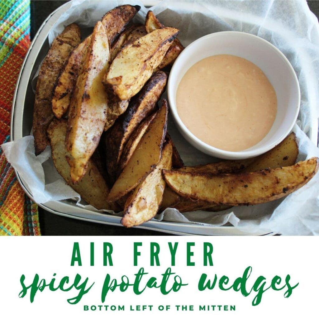 overhead shot of air fryer spicy potato wedges with sauce and image text overlay.