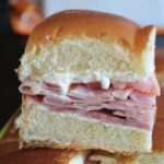 zoomed in shot of a ham slider sandwich on Hawaiian rolls stacked on more sandwiches.