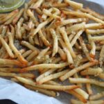zoomed in side shot of french fries drizzled with pesto sauce mixed with butter and parmesan cheese on a piece of parchment paper on a pan.