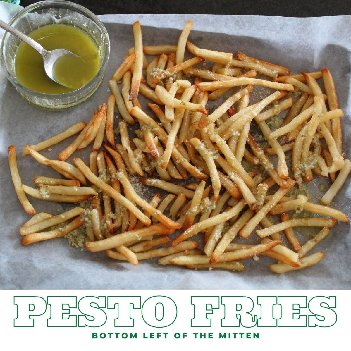 collage image of overhead shot of a pan of pesto fries with parchment paper underneath and a dish of pesto butter off to the side and descriptive text overlay.