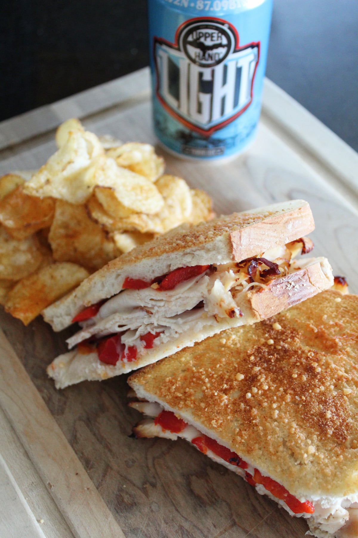 A roasted pepper turkey sandwich cut in half ready to eat with a craft beer in the background.