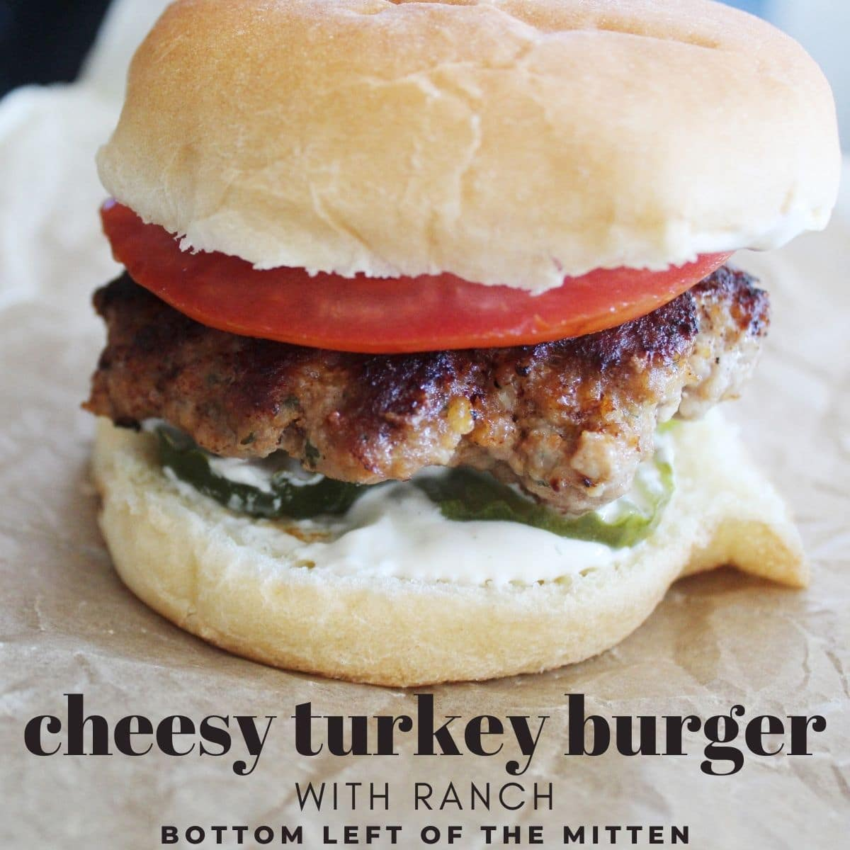 zoomed in shot of a cheesy turkey burger on a bun with ranch dressing tomato and pickles with descriptive text overlay.