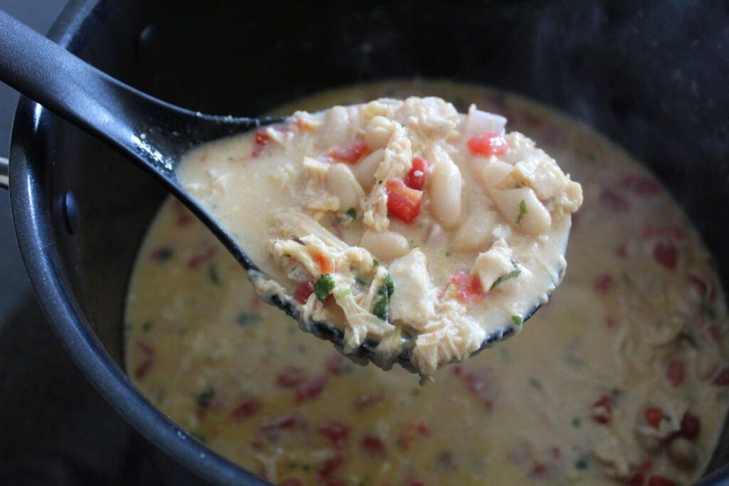 creamy chicken chili in a ladle.