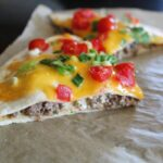 side shot of individual tortilla pizza on parchment paper.