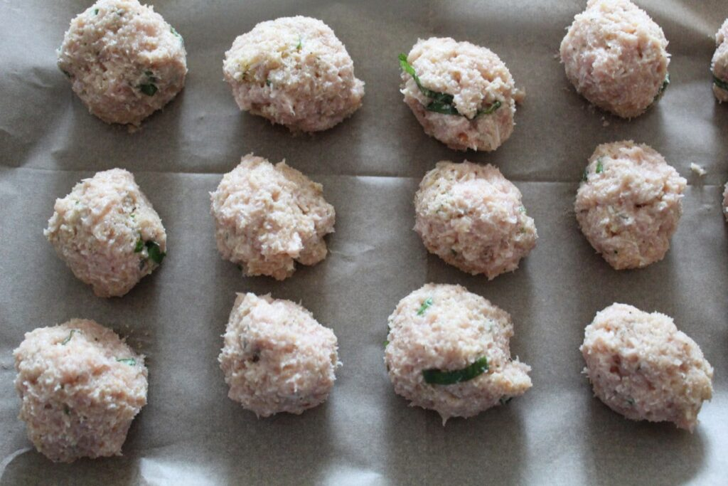 overhead shot of meatballs on a baking sheet.