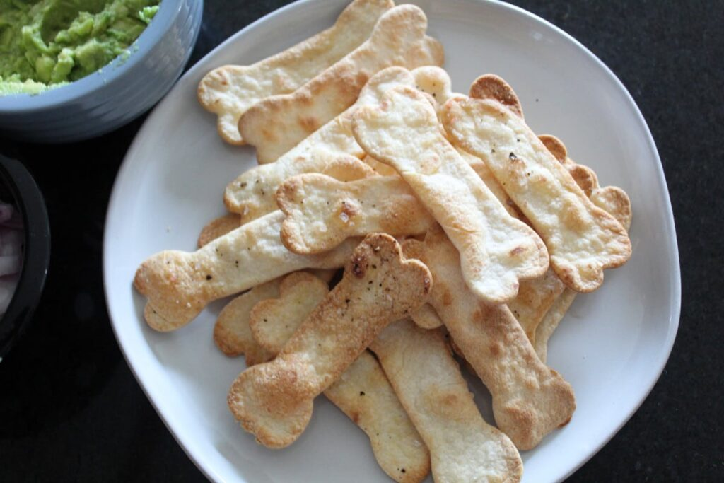 baked dog  bone tortilla chips on a plate.