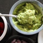 easy guacamole dip on a spoon with bowls placed around it.