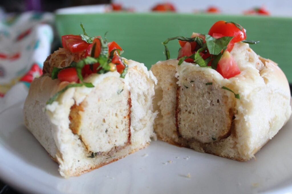 side shot of a Caprese topped meatball sub on a plate.